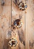 巧克力给油炸圈饼上釉用在木背景,顶视图的榛子 免版税库存照片