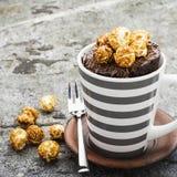 巧克力芳香杯子蛋糕用喝在灰色石背景的秋天舒适温暖的茶的焦糖开胃玉米花 库存照片
