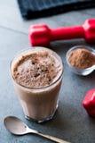 巧克力蛋白质与乳清蛋白粉末和红色哑铃的震动圆滑的人 图库摄影