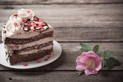 巧克力蛋糕与在老木背景上升了 免版税图库摄影