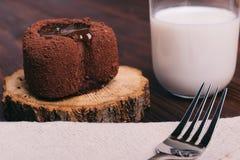 巧克力蛋糕和杯在一张棕色桌上的牛奶,在t的叉子 免版税库存照片