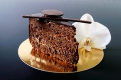 巧克力蛋糕片断与巧克力奶油的在与一朵白色兰花花的一块金黄餐巾 免版税库存图片