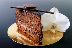 巧克力蛋糕片断与巧克力奶油的在与一朵白色兰花花的一块金黄餐巾 库存照片