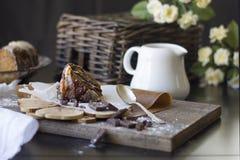 巧克力蛋糕片断与果仁糖和焦糖结冰的木表面上 免版税库存照片