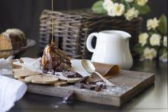 巧克力蛋糕片断与果仁糖和焦糖结冰的木表面上 库存照片