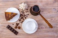 巧克力蛋糕片断的顶视图在一个茶碟和一个杯子的咖啡咖啡、一个碗有糖立方体的,咖啡豆、茴香和ch的 库存图片