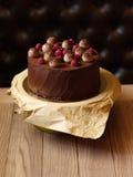 巧克力蛋糕特写镜头用莓,黑醋栗,洒与在棕色木背景的可可粉 免版税库存图片