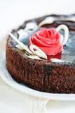 与乳脂状的桃红色玫瑰的巧克力蛋糕 免版税库存照片