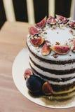 巧克力蛋糕用无花果和坚果在一张木桌上 库存图片