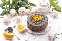 巧克力蛋糕用桔子和结冰 在白色背景和白玫瑰花束  早晨好以惊奇和 库存照片