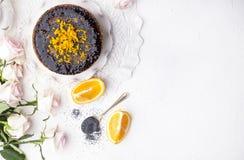 巧克力蛋糕用桔子和结冰 在白色背景和白玫瑰花束  早晨好以惊奇和 免版税库存照片