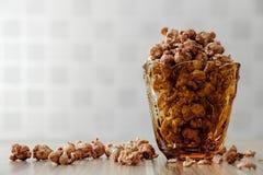 巧克力调味了玉米花在黄色玻璃和在棕色木桌上有桂香背景 库存照片