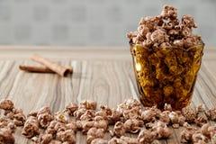 巧克力调味了玉米花在黄色玻璃和在棕色木桌上有桂香背景 免版税库存照片