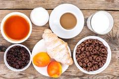 巧克力谷物剥落,咖啡、牛奶、新月形面包和果子b的 库存图片