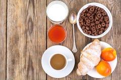 巧克力谷物剥落,咖啡、牛奶、新月形面包和果子b的 库存照片