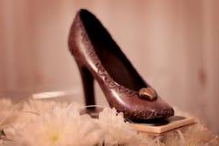 巧克力鞋子和花有模糊的背景 免版税库存照片