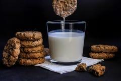 巧克力饼干和牛奶,在黑背景 免版税库存图片