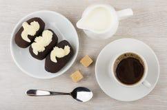 巧克力饼干结块与在茶碟,水罐牛奶, co的buttercream 免版税库存照片