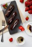 巧克力饼用在黑色页岩的新鲜的草莓 小饼点心用莓果和咖啡在白色背景 免版税库存照片