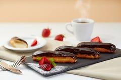 巧克力饼用在黑色页岩的新鲜的草莓 小饼点心用莓果和咖啡在白色背景 免版税库存图片