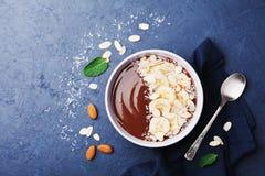 巧克力香蕉杏仁椰子在黑暗的石台式视图的圆滑的人碗 健康早餐或点心 平的位置 免版税库存图片