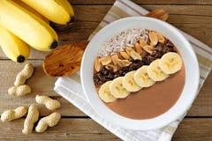 巧克力,花生酱,香蕉,在土气木头的圆滑的人碗顶上的场面 免版税图库摄影