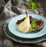 巧克力绉纱用在糖浆的水煮的梨 库存图片