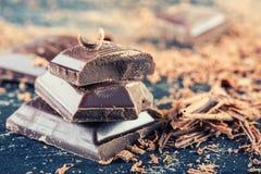 巧克力 黑色巧克力 黑巧克力一些个立方体与薄荷叶的 从溢出的巧克力平板磨碎了chockolate粉末 库存图片