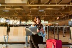 巧妙的坐在终端大厅里的电话和膝上型计算机的女性乘客 库存图片