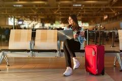 巧妙的坐在终端大厅里的电话和膝上型计算机的女性乘客 免版税库存图片