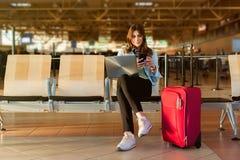 巧妙的坐在终端大厅里的电话和膝上型计算机的女性乘客 免版税库存照片