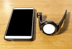 巧妙的手表和智能手机在桌上 库存照片