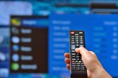 巧妙的电视和手 免版税库存照片