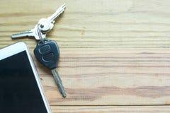 巧妙的电话、汽车遥远的钥匙和钥匙在木背景 免版税库存图片
