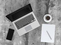 巧妙的电话、膝上型计算机和咖啡杯在具体地面 免版税库存照片