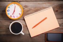 巧妙的电话、闹钟、咖啡和笔记本 免版税库存图片