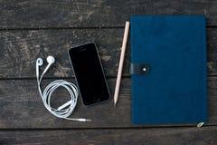 巧妙的电话和笔记本在书桌上 库存照片