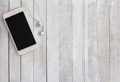 巧妙的电话和耳机在白色木背景 免版税图库摄影