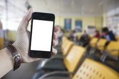 巧妙的电话在手中有迷离运输站的 免版税库存图片