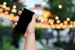 巧妙的电话在手中有bokeh的在公园背景中 并且安排一些空间为写字词 库存图片