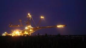 巨型挖掘机在一个煤炭露天开采矿晚上 免版税库存图片
