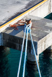 巨型蓝色绳索被栓对生锈的系船柱 免版税库存照片