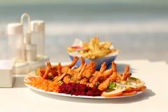 巨型虾服务用沙拉和炸薯条在海滩 免版税图库摄影