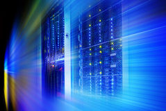 巨型计算机在一系列的数据中心设备的磁盘存储 背景迷离弄脏了抓住飞碟跳的行动 库存照片