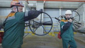巨大的圆的杠杆的人在精炼厂的管子 股票视频