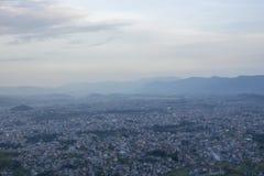 巨大的城市谷的看法在山的剪影的背景的在晚上在重的天空下 库存照片