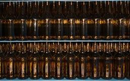 巨大的堆在蓝色桌上的空的玻璃瓶 库存照片