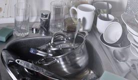 巨大的堆未洗的盘在厨房水槽和在工作台面 很多器物和厨房器具在洗涤前 图库摄影