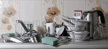 巨大的堆未洗的盘在厨房水槽和在工作台面 很多器物和厨房器具在洗涤前 免版税图库摄影