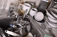 巨大的堆未洗的盘在厨房水槽和在工作台面 很多器物和厨房器具在洗涤前 库存照片
